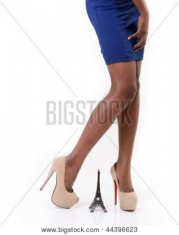 Parisian - beautiful long legs african model standing on high heels near little Eiffel tower, over white