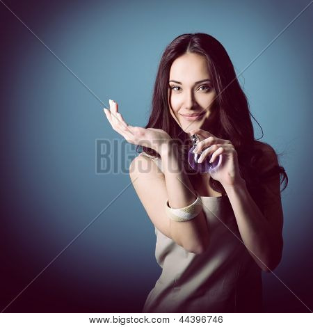 Woman with perfume, young beautiful girl holding bottle of perfume and smelling aroma, over blue purple background