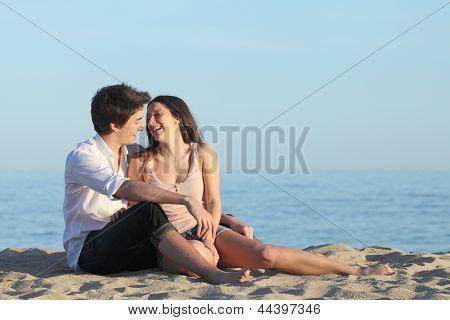Casal sentado e rindo na areia da praia