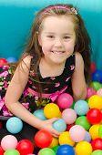 Постер, плакат: Счастливый маленькая девочка сидит в яркие шарики