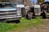 stock photo of junk-yard  - Old rusted car and tractor in junk yard - JPG