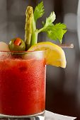 foto of bloody mary  - bloody mary cocktail isolated on a busy bar top garnished with onions olives asparagus and celery - JPG
