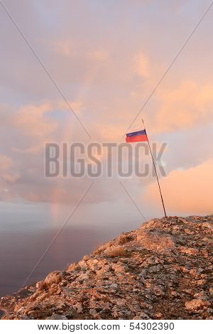 Russian Flag On The Top Of A Mountain On The Background Of The Sea With A Rainbow