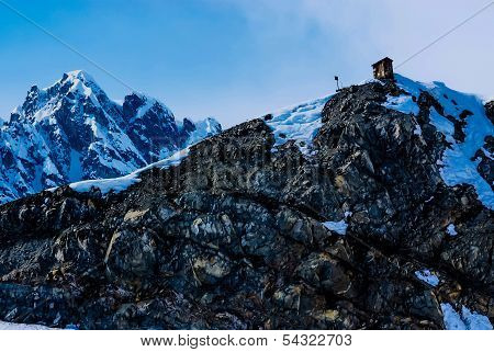 A Mountain Outhouse Pearched on a Snow Covered Mountain Peak in Alaska