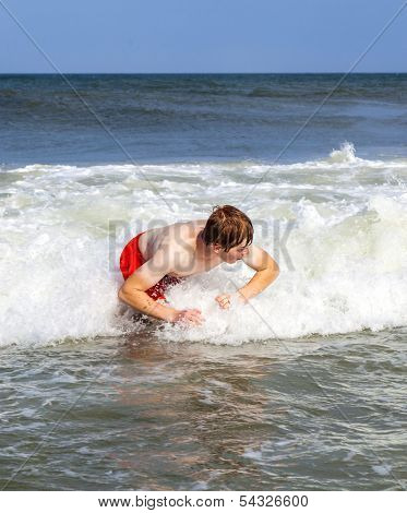 Boy Has Fun Jumping In The Waves