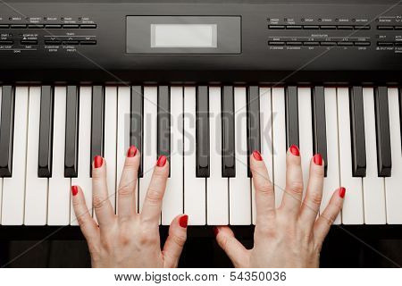 hands playing digital piano synthesizer