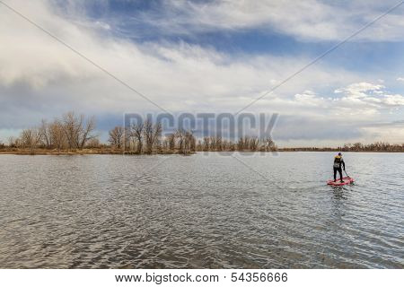 a calm lake in late fall scenery with a lonely male stand up paddler