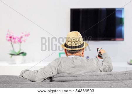 Man with hat sitting on a sofa and changing TV channels at home