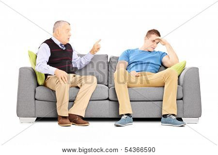 Father reprimending his son seated on a couch isolated on white background