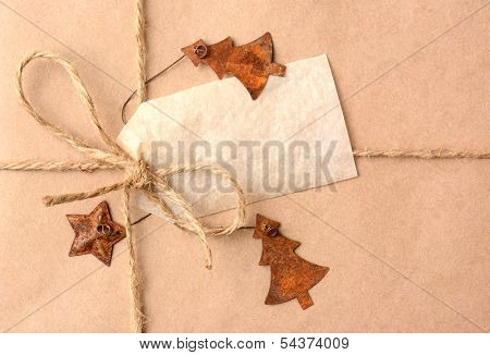 Closeup of a gift tag on a Christmas present. The package is wrapped in plain brown paper with a tied with twine. The package is adorned with metal star and christmas tree ornaments. Horizontal
