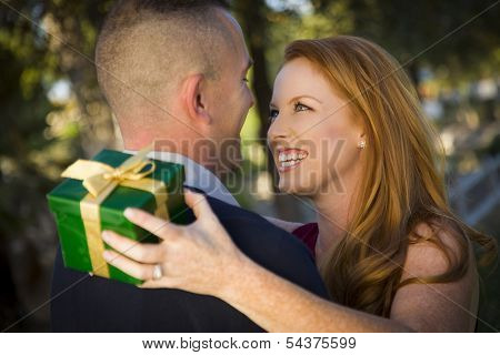 Smiling Beautiful Young Woman and Handsome Military Man Exchange a Christmas Gift.
