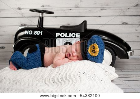 Newborn Baby Wearing A Policeman Costume