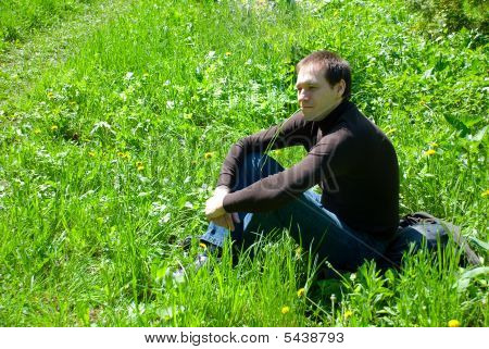 A young man sitting on green grass