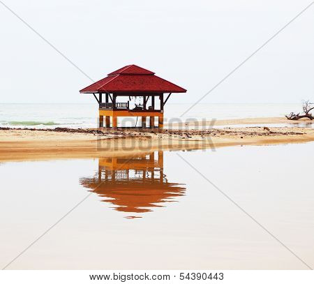 Sandy beach on Koh Samui. The beach wooden arbor is picturesquely reflected in water