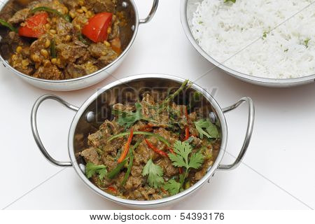A bowl of spiced lamb curry with coriander leaves and slivers of red and green chillies, next to a bowl of Lahore-style lamb curry with split peas and some rice.