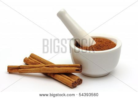 Grounded Cinnamon In A Bowl With Cinnamon Sticks