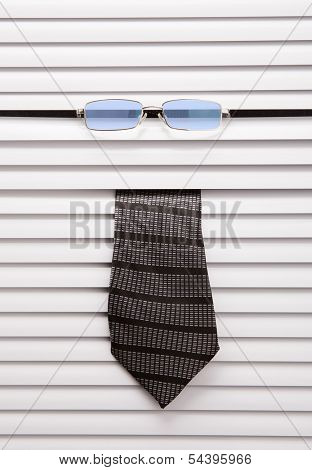 Tie and glasses sticking out of the window blinds
