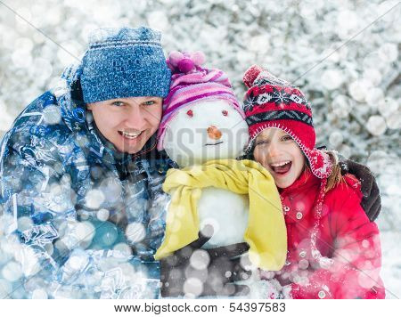 Father and daughter making a snowman