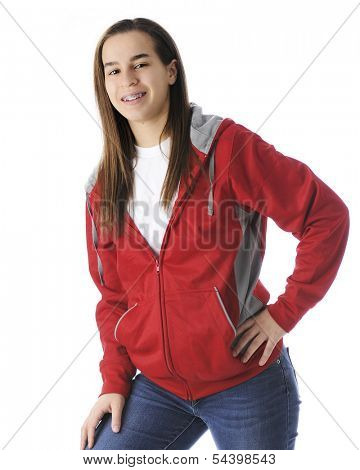 A slim teen athlete happily standing with her foot propped on her basketball.  On a white background.