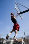 stock photo of slam  - A young basketball player driving to the hoop for a slam dunk - JPG