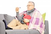 Sick mature man on a sofa with a hot-water bottle looking at thermometer isolated on white backgroun