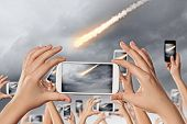 People taking photos of falling meteorite on mobile phone camera