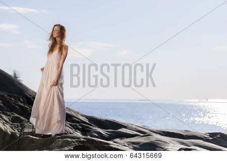 Young Woman On Rocky Shore