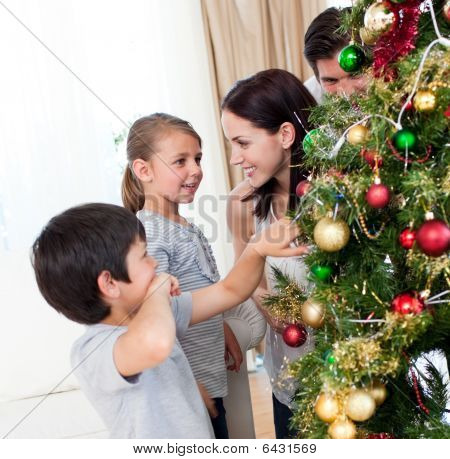 Smiling Family Decorating A Christmas Tree With Baubles