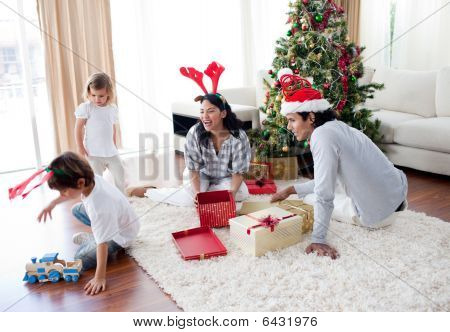 Family Playing With Christmas Gifts At Home
