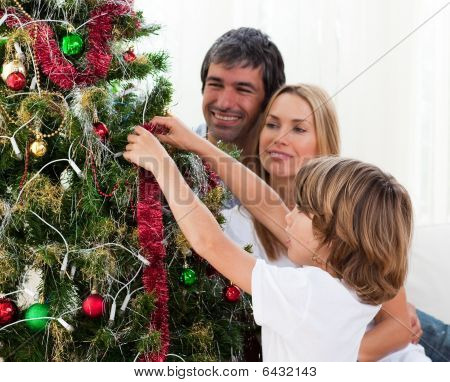 Little Boy Hanging Christmas Decorations With His Parents