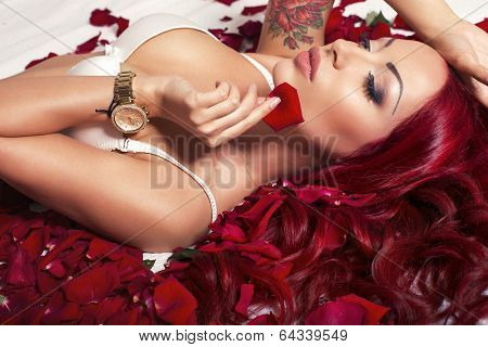 sexy woman with red hair lying on rose's petals