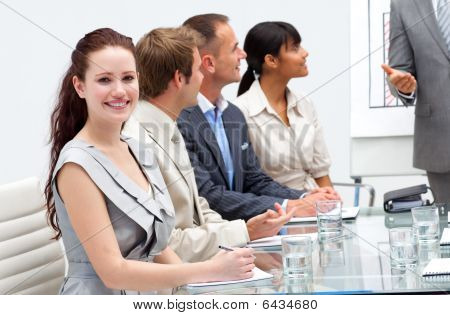 Smiling Businesswoman Listening To His Colleague Giving A Presentation