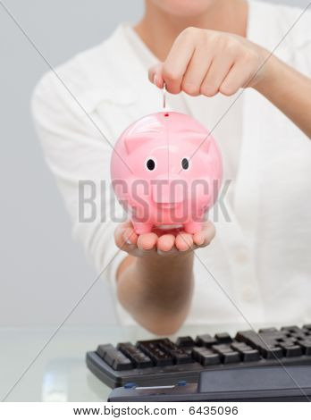 Close-up Of A Businesswoman Saving Money In A Piggibank
