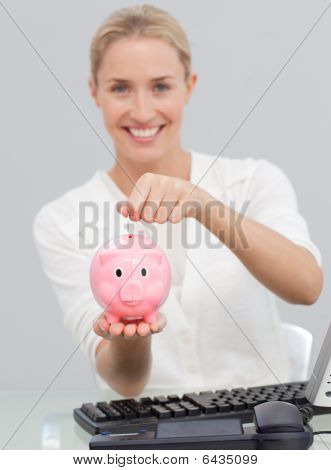 Smiling Businesswoman Saving Money In A Piggibank