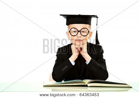 Serious schoolboy in academic hat sitting at the table with a book. Isolated over white.