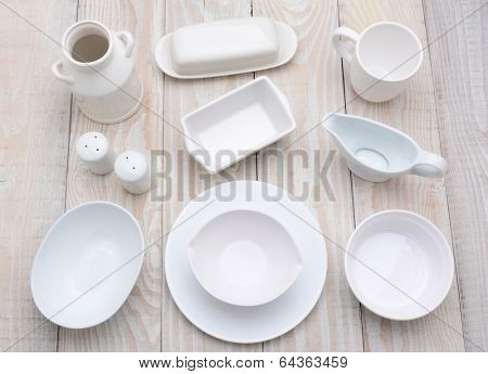 High angle shot of different dinnerware items,  of varying shades of white.  Horizontal format on a rustic whitewashed farmhouse style kitchen table.