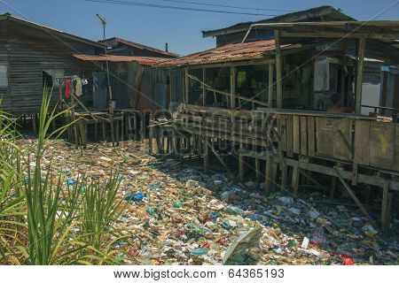 KOTA KINABALU, MALAYSIA - APRIL 26 2014: Pollution in shanty town. Photo showing environmental problem of garbage build up in poor shanty town due to lack or refuse collection or recycling services.