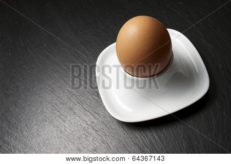 Closeup of a brown egg on a table slate.