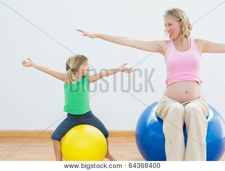 Pregnant woman bouncing on exercise ball with young daughter in a fitness studio