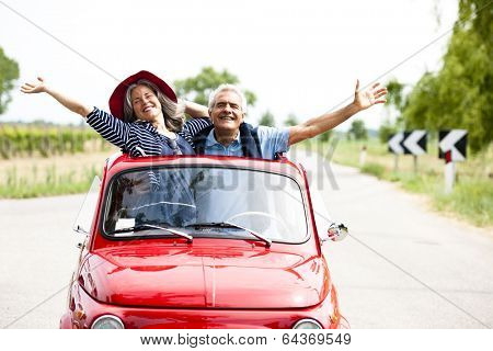 Happy senior couple driving vintage car