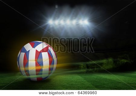 Football in french colours against football pitch under spotlights