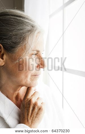 Portrait of a pensive senior woman looking outside the window