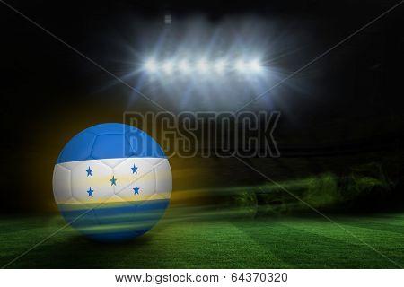 Football in honduras colours against football pitch under spotlights