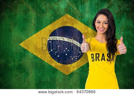 Pretty football fan in brasil tshirt against brazil flag in grunge effect