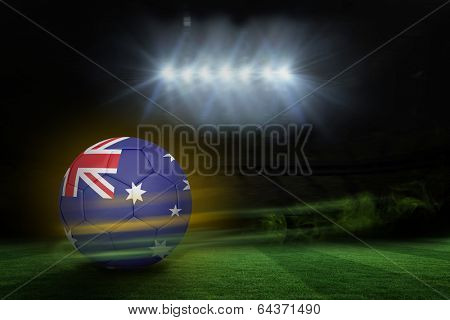 Football in australia colours against football pitch under spotlights