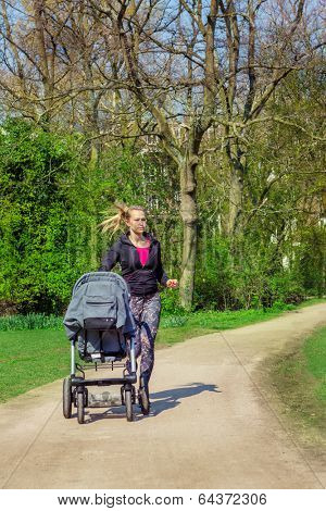 Active young woman jogging in a park with a baby buggy