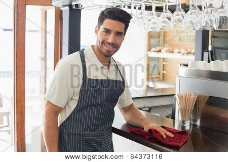 Portrait of a young smiling waiter cleaning countertop with sponge