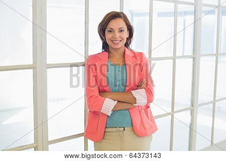 Portrait of a confident young businesswoman with arms crossed standing at a bright office