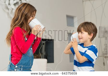Cute Little Boy Listening To His Sister Speaking Through Tin Can Phone