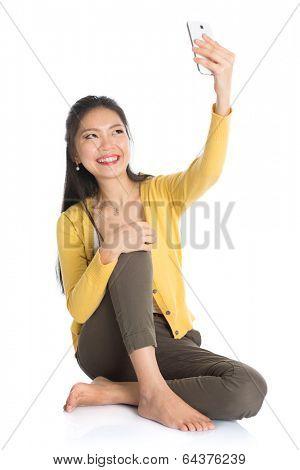 Full body Asian girl selfie or self photographing, sitting on floor, isolated white background.